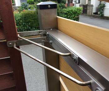 重いコンクリート境界ブロックの土台でも大型台風には耐えられなかったため、フェンスの角を先に設置した目隠しフェンスとL字型に接続しました。固定した金具は、ステンレス製のこちらはステンレス製の棚受けを活用しています。