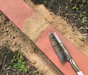 固まる防草砂の硬化時間は24時間となっており、翌日の14〜16時間程度のこの段階では、幸いまだカチカチになっていません。ワイヤーブラシで優しくこすることで、なんとか目地を綺麗にすることができました。